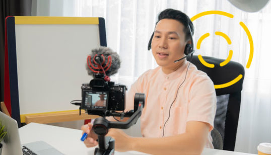 Man recording and presenting a corporate training video in his office.