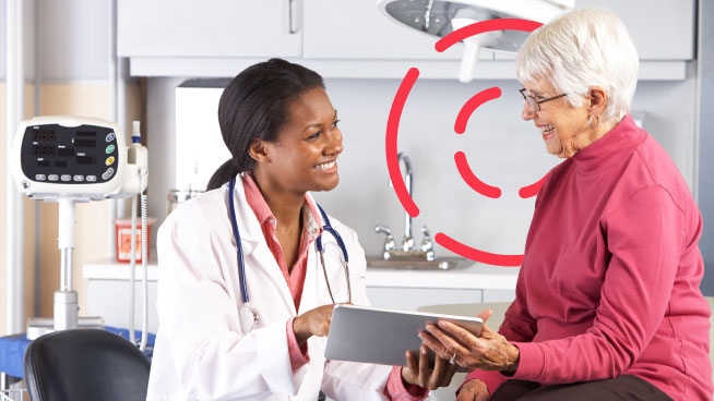 Patient Engagement in Healthcare - A doctor sits with an older patient over a tablet