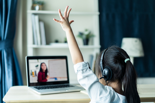 Young student raising her hand while using online teaching platforms for teachers